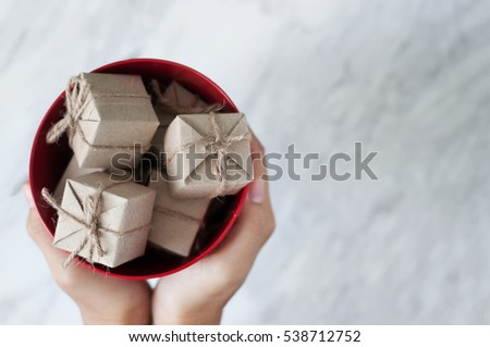 Woman hands holding gift boxes in red bucket on white marble background, Christmas and New Year concept. copy space.