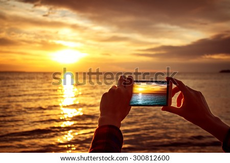 woman hands holding mobile phone at sunset