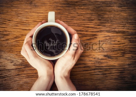 woman hands holding mug of hot drink that standing on wooden table