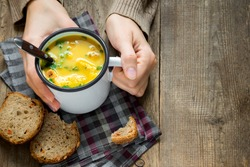 Woman hands holding mug of vegetable soup with parsley and croutons over wooden background - healthy winter vegetarian food