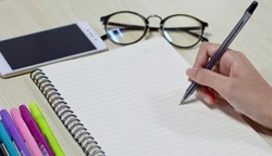Woman hands holding paper sheet or notebook and pen. White table. Top view. work with glasses and telephone. Woman hands writing on book in office. Copy space.