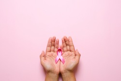 Woman hands holding pink ribbon over pink background, breast cancer awareness, October pink concept