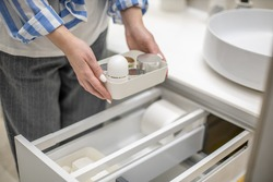 Woman hands holding plastic container with creams and placing into the bathroom drawer. Concept of using toiletry organizer for keeping or organizing personal hygiene accessories with KonMari method.