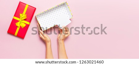 Woman hands holding present red box with gold ribbon on pink background Flat lay top view. Present for birthday, surprise, valentine day, Christmas, New Year. Congratulations background copy space. #1263021460