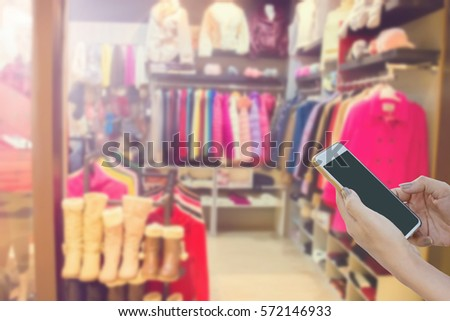 woman hands holding, using mobile phone at winter clothing store blurred background  #572146933