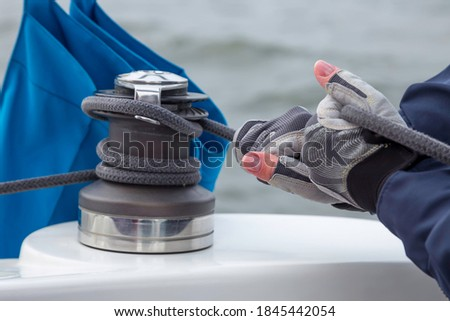 Woman hands in gloves holding the rope on sailing boat yacht sheet winch closeup on water sea background Stock photo ©