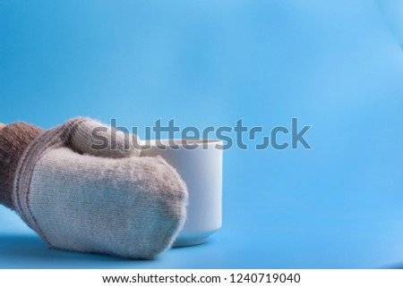 Woman hands in mittens hold cup #1240719040