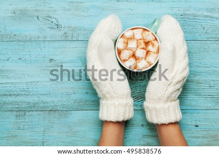 Woman hands in mittens hold cup of hot cocoa or chocolate with marshmallow on turquoise vintage table from above. Flat lay style.  #495838576