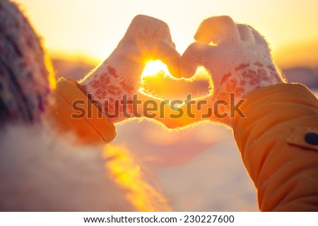 Woman hands in winter gloves Heart symbol shaped Lifestyle and Feelings concept with sunset light nature on background #230227600