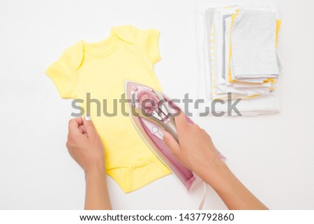 Woman hands ironing clean, crumpled yellow bodysuit on white board. Daily routine. Preparing things in pregnancy time. Modern electric iron with steam system. Closeup. Point of view shot. #1437792860