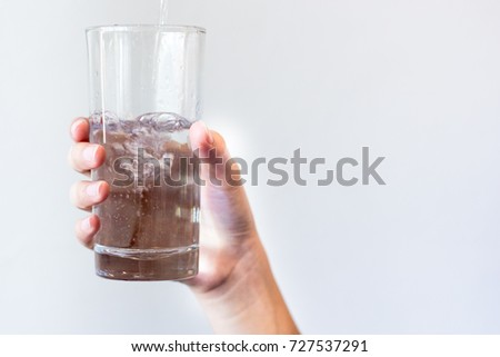 Woman hands isolated holding a glass of water while pouring water into glass on grey and white background. A half glass of water. - Shutterstock ID 727537291