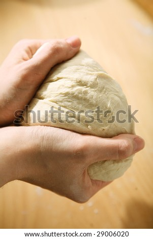 Woman hands kneading dough on the table