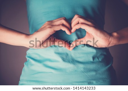 Woman hands making a heart shape on her stomach, healthy bowel degestion, probiotics and prebotics  for gut health, organ donor day