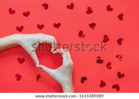 Woman hands making heart shape on red background with red red hearts