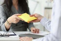 Woman hands over full envelope to her interlocutor. Salary in an envelope concept