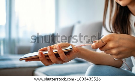 Woman hands plugging a charger in a smart phone. Woman using smartphone with powerbank. Young woman charging power to smart phone. Woman charging battery on mobile phone at home Foto stock ©