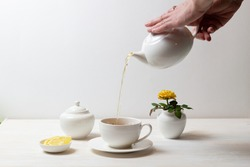 woman hands pouring tea in cup with saucer from tea pot, sugar bowl, yellow rose in milk jug and lemon on white background