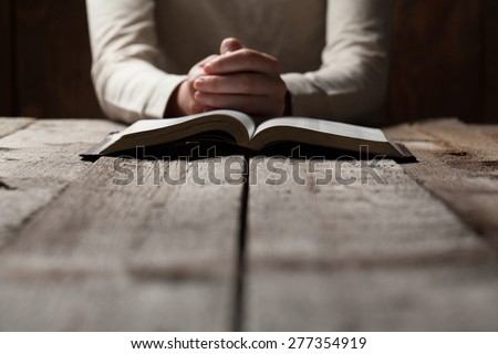 Woman hands praying with a bible in a dark over wooden table - Shutterstock ID 277354919