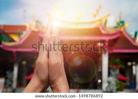 Woman hands pressing together praying and blessing in front of  chinese shrine with sunlight and bokeh.Faith and religious.