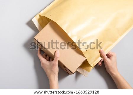 Woman hands puting  cardboard box inside of large postal envelop Foto d'archivio ©