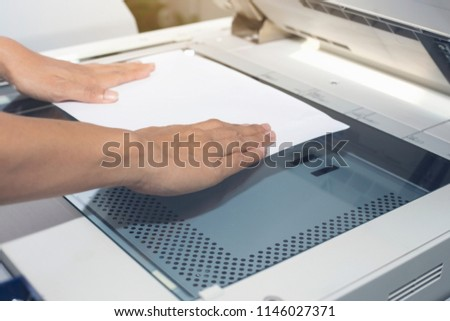 woman hands putting a sheet of paper into a copying device #1146027371