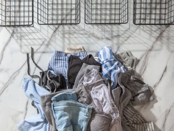 Woman hands putting stack of clean clothes for neatly tidying up and placing in steel wire wardrobe baskets organiser on the white marble table. Marie Kondo style and space saving storage concept.