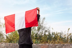 Woman hands raising the national flag of Peru into the air