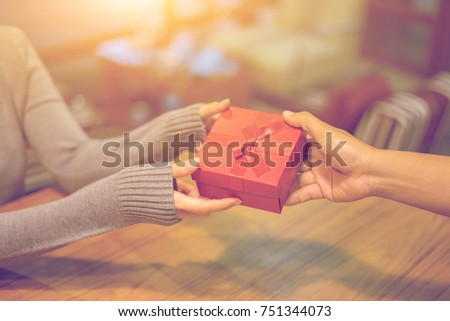 Woman hands receiving package gift box from a man - delivery and courier concepts,preparing gifts for Christmas