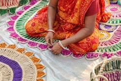 Woman hands sewing handmade jute carpets for sale at a handicraft fare at Kolkata India