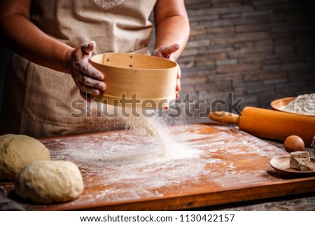 Woman hands sifting flour with flour filter #1130422157