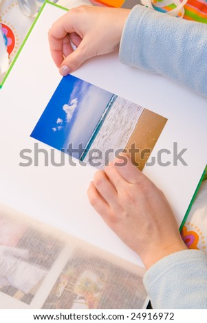 Woman hands sticking images in her photo album. Images can be replaced.