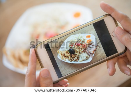 Woman hands taking food photo by mobile phone. Food photography. Share food photography. Thai food. Popular food. Delicious food.