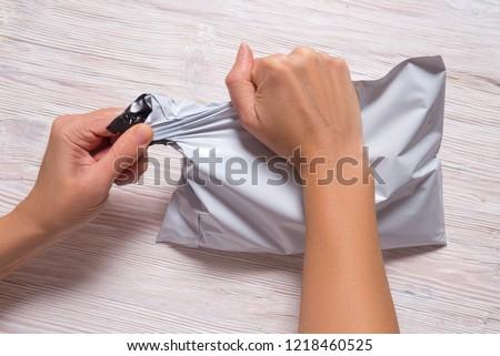 woman hands tear polythene envelope Foto d'archivio ©