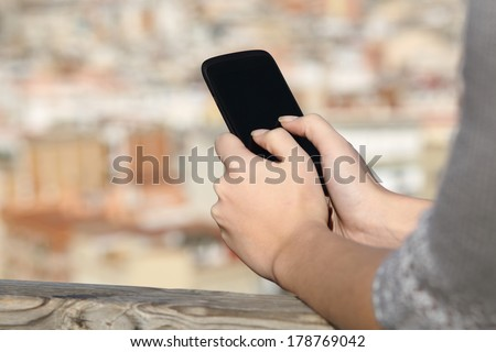 Woman hands texting on a smart phone screen with an urban background #178769042