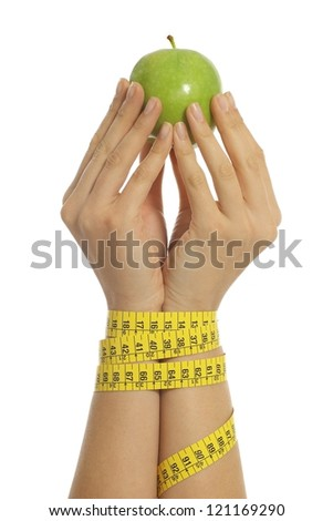 Woman hands tied with measure tape holding an apple on a white isolated background