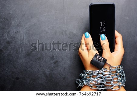 Woman hands tied with metallic chain with padlock on dark background suggesting internet or social media addiction