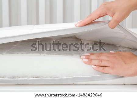 Woman hands touching different layers of new white mattress. Foam rubber and buckwheat inside. Mother checking hardness and softness of baby bed. Choice of the best type and quality. Closeup.