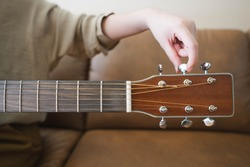 Woman hands tuning acoustic guitar strings before playing music lesson at home. Close up.