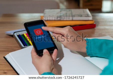 Woman hands turning off mobile phone, to be able to draw. Woman touching cell phone screen, to turn it off. I disconnect to live a healthier life Photo stock ©