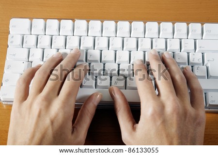 woman hands typing on a wireless white keyboard computer posed on a table