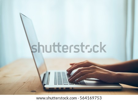 Woman hands typing on laptop keyboard at the office, Woman worker and business concept, Soft focus on vintage wooden table.