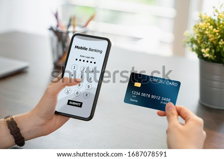 Woman hands using mobile banking on smartphone with holding credit card and enter password to login application.