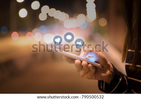 Woman hands using mobile smartphone in the street with icon social media and social network. - Shutterstock ID 790500532