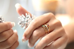 Woman Hands wearing many gold gems ring on the fingers with snow pine cones on the reflection table