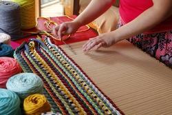 Woman hands weaving a handmade carpet