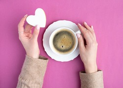 Woman hands with a cup of coffee and heart biscuit