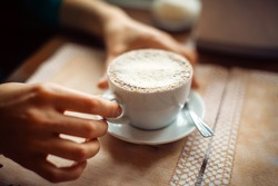 woman hands with cappuccino on a table