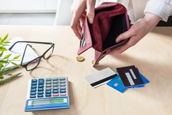 Woman hands with empty wallet, a few coins and credit cards on the table with calculator. Unemployment and dismissal concept. Money crisis.