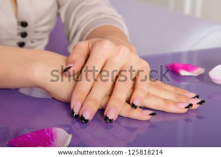 Woman hands with french manicure with crystals and rose petals