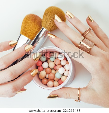 woman hands with golden manicure and many rings holding brushes, makeup artist stuff stylish, pure close up bright